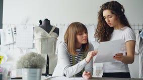De professionele vrouwelijke manierontwerpers bekijken schets en bespreken details van toekomstige kleren productief stock video