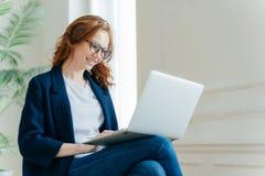 De professionele vrouwelijke werkgever geniet van werkend proces, zit gekruiste benen met laptop apparaat, online babbelt, heeft  royalty-vrije stock foto