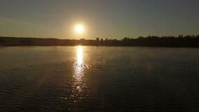 De professionele zwemmer zwemt bij zonsondergang in langzame motie stock videobeelden