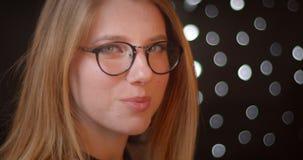 De profielspruit van blondemodel in glazen met heldere samenstelling glimlacht schuchter en prettily op bokehachtergrond stock footage