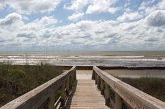 De promenade die tot het strand op een bewolkte dag leiden Stock Afbeeldingen