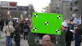 De protesteerders zijn op de straat in de stad Ernstige volwassen jonge mens met een groene banner in handen stock footage