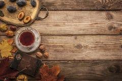 De pruimen, de noten en de bladeren met uitstekend notitieboekje en de thee met filmfilter voeren achtergrond uit Stock Afbeelding