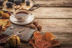 De pruimen, de noten en de bladeren met uitstekend notitieboekje en de thee met filmfilter voeren close-up uit Royalty-vrije Stock Foto