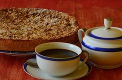 De pruimkruimeltaart scherp met kop van koffie en de suiker werpen op rode achtergrond Royalty-vrije Stock Foto