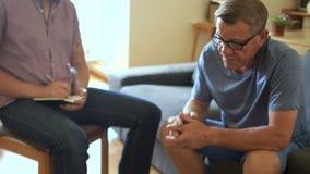 De psycholoog neemt nota's tijdens een therapeutische zitting De patiënt vertelt met droefheid en golven hopeloos met zijn hand stock video