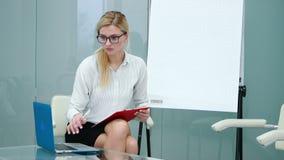 De psycholoog op het werk wacht op de cliënt en maakt document baan stock videobeelden