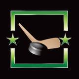 De puck en de stok van het hockey op groen sterframe Stock Afbeelding