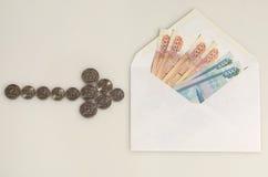 De punten van de muntstukkenpijl aan envelop met geld Stock Fotografie