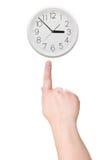 De punten van de vinger aan de klok Stock Afbeelding