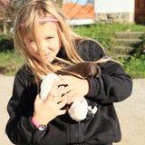 De puppy holded in jonge geitjeshanden Stock Foto