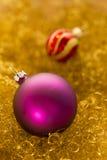 De purpere en rode Kerstmisballen op goud schitteren Stock Afbeelding