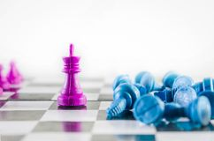 De purpere koning haalde blauw team in een schaakbord neer stock foto