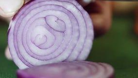 De purpere ui wordt die in ringen met scherp mes op groene keukenlijst wordt gehakt stock videobeelden