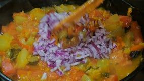 De purpere Ui wordt toegevoegd aan de vegetarische schotel, bewegend met een houten lepel stock video