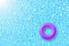 De purpere vlotter van de zwembadring in blauw water en heldere zon royalty-vrije stock foto's