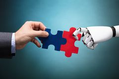De Puzzel van Businesspersonand robot holding stock afbeelding