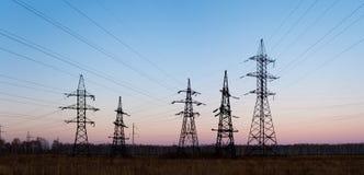 De pylonen en de lijnen van de elektriciteit bij schemer. Royalty-vrije Stock Fotografie