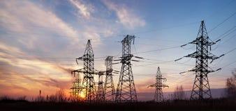 De pylonen en de lijnen van de elektriciteit bij schemer. Royalty-vrije Stock Afbeeldingen