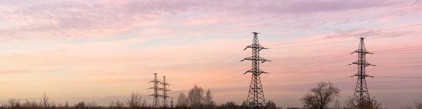 De pylonen en de lijnen van de elektriciteit bij schemer. Panorama. Royalty-vrije Stock Afbeelding