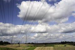 De pylonen van de elektriciteit in een landbouwlandschap Stock Foto's