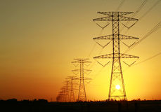 De Pylonen van de elektriciteit tegen Zonsondergang Stock Foto