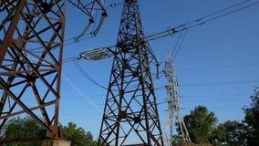 De pylonen van een hoogspanningsmacht tegen blauwe hemel stock video