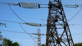 De pylonen van een hoogspanningsmacht tegen blauwe hemel stock footage