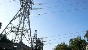 De pylonen van een hoogspanningsmacht tegen blauwe hemel stock videobeelden