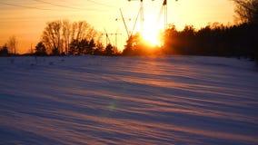 De pylonen van de elektriciteit op gerstgebied Machtslijn bij zonsondergang op het gebied van de de wintersneeuw Energievoorzieni stock videobeelden