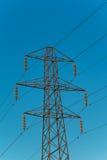 De pyloon van de elektriciteit tegen een blauwe hemel Royalty-vrije Stock Afbeelding