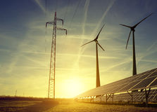 De pyloon van de elektriciteitstransmissie met zonnepanelen en windturbines Stock Fotografie
