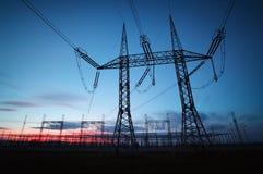De pyloon van de elektriciteitstransmissie tegen blauwe hemel bij D wordt gesilhouetteerd die Royalty-vrije Stock Fotografie