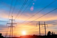 De pyloon van de elektriciteitstransmissie die tegen blauwe hemel wordt gesilhouetteerd Hoogspanningspost voor achtergrond stock fotografie