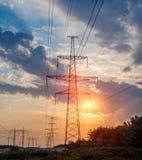 De pyloon van de elektriciteitstransmissie tegen blauwe hemel bij schemer wordt gesilhouetteerd die stock afbeelding