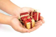 De röda gåvaaskarna & guld- färg i hand ger sig för dig på vit bakgrund Royaltyfria Bilder