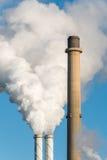 De röka rören av en fabrik Arkivbild