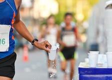 De raceauto die van de marathon kop van water vangt Stock Fotografie