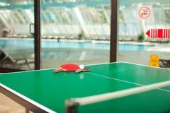 De rackets van het pingpong en bal swimmig pool Stock Afbeelding