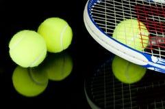 De racketten van het tennis en 3 ballen Stock Foto's