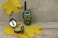 De radio en het kompas liggen op de gele esdoornbladeren Houten achtergrond stock afbeeldingen