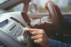 de radio van de hand het open auto luisteren Veranderende draaiende de knoopradiostations van de autobestuurder op Zijn Voertuigs stock afbeelding