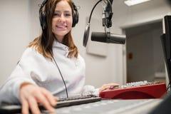 De radiohoofdtelefoons van Jockeysmiling while wearing in Studio royalty-vrije stock afbeeldingen