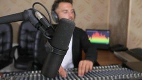 De radiopresentator in oortelefoons in voorzijde van audioconsole op radiostudio unfocused binnen achtergrond stock footage