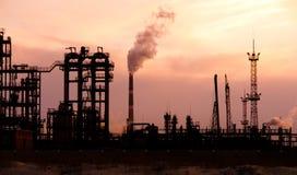 De raffinaderij van de olie bij zonsondergang. De verontreiniging van het milieu. Stock Foto