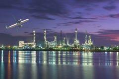 De raffinaderijinstallatie van de tankerolie bij schemering met vliegtuig die over vliegen Royalty-vrije Stock Afbeeldingen
