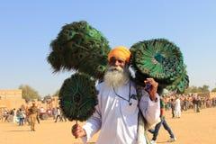 De Rajasthanidorpsbewoner verkoopt pauwveren Stock Afbeeldingen