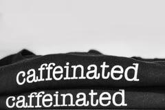 De rand van twee gevouwen zwarte t-shirts met het woord caffeinated van beide tonen gevouwen en gestapeld bij bodem van kader met royalty-vrije stock afbeelding