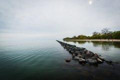 De randlandschap van het water met zich rots het uitrekken in de afstand stock foto's