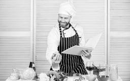 De recepten van de boekfamilie Volgens recept Kokende voedsel van de mensen het gebaarde chef-kok Kerel gelezen boekrecepten Culi stock fotografie